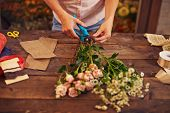 Female florist cutting stems of flowers in workshop