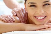 Happy woman looking at camera during spa procedure