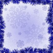 blue frame from tinsel on snowflake background