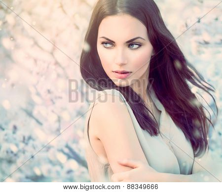 Fashion girl outdoor portrait in blooming trees. Beauty spring Romantic woman in flowers. Sensual La