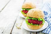stock photo of quinoa  - Quinoa beet and chickpea burgers on a white wood background - JPG