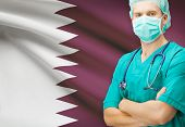 stock photo of qatar  - Surgeon with national flag on background  - JPG
