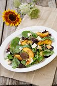 stock photo of vinegar  - Plate of grilled peach and Mozzarella salad with mixed baby greens and balsamic vinegar in a rustic setting - JPG