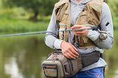 Постер, плакат: Fishing in river A fisherman with a fishing rod on the river bank