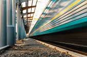 foto of passenger train  - High speed passenger train on tracks with motion blur effect at sunset - JPG