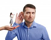 stock photo of ear  - surrealism photo of hand holding small woman with megaphone that yelling at the man with big ear - JPG