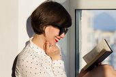 stock photo of daydreaming  - Girl with sunglasses daydreaming sitting by the window - JPG