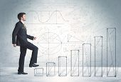 picture of climb up  - Business man climbing up on hand drawn graphs concept on background - JPG