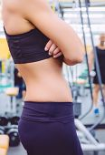 stock photo of health center  - Closeup of sporty woman with slim waist and black sportswear over a fitness center background - JPG