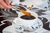 stock photo of white sugar  - Coffee from a beautiful black and white teapot - JPG