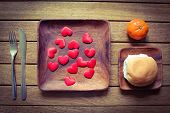 picture of satsuma  - A wooden place set with red love hearts a bread roll and an orange