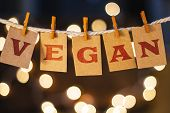 pic of glow  - The word VEGAN printed on clothespin clipped cards in front of defocused glowing lights - JPG