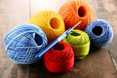 stock photo of hook  - Colorful yarn for crocheting and hook on wooden table  - JPG