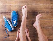 image of knee-cap  - Unrecognizable injured runner sitting on a wooden floor background - JPG