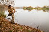 pic of fishermen  - Young fisherman fishing on the river bank - JPG