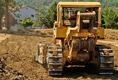 pic of bulldozers  - Large bulldozer moving rock and soil for a fill lift at a new commercial development road construction project - JPG