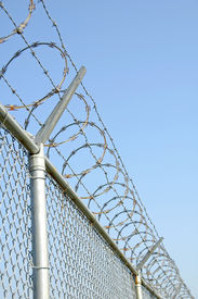 stock photo of barbed wire fence  - chain link security fence with razor wire on top - JPG