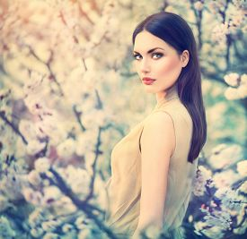 stock photo of orchard  - Spring fashion girl outdoors portrait in blooming trees - JPG