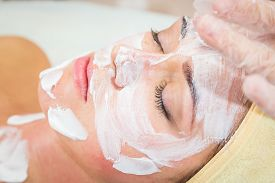 foto of beauty parlour  - Beautiful woman with facial mask at beauty salon - JPG