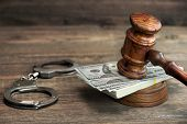 Dollar Banknotes, Handcuffs And Judge Gavel On Wood Table poster