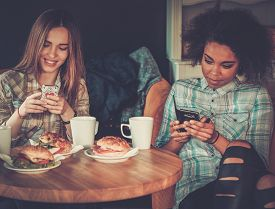 picture of cell  - Multiracial girls with cell phones in a cafe  - JPG