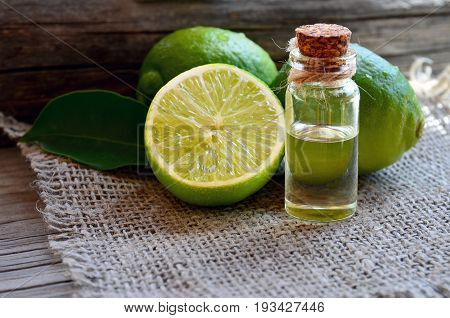poster of Lime essential oil in a glass bottle with fresh lime fruits.Lime oil for spa,aromatherapy and bodycare.Extract oil of lime.Selective focus.