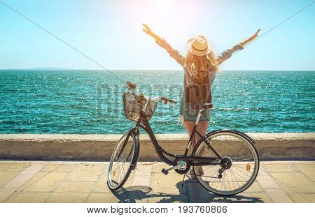 poster of Blonde woman in summer hat with her bicycle walking coastline by the sea beach. Sea view. Freedom. W