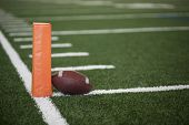 Selective focus photo of the pylon and touchdown line on a football field. Low angle view from the e poster