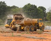 stock photo of oversize load  - bucket loader loading rock into hauler - JPG