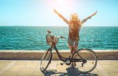 Blonde woman in summer hat with her bicycle walking coastline by the sea beach. Sea view. Freedom. W poster