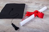 Graduation Cap, Hat With Degree Paper On Wood Table Graduation Concept poster