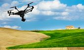 A flying drone with camera with blured hills of Tuscany in the background poster