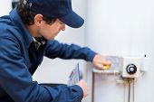 Plumber repairing an hot-water heater poster