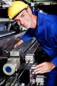 stock photo of blue-collar-worker  - happy modern industrial machine operator at work - JPG