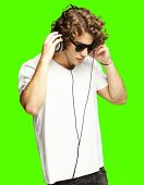 portrait of a handsome young man listening music against a removable chroma key background