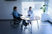 Front view of mature Caucasian female doctor and disabled Caucasian patient in wheelchair discussing poster