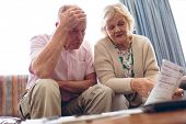 Front view of worried senior Caucasian couple discussing over medical bill while sitting on sofa at  poster