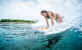 Happy young woman learns surfing in the tropics poster