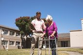 Low angle view of a Caucasian male doctor helping senior Caucasian woman with her walker at backyard poster