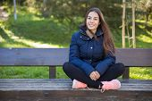 Smiling Pretty Sporty Woman Posing At Camera On Bench. Pretty Young Lady Wearing Sportswear And Sitt poster