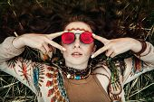 A portrait of a fashion female model lying on the grass. Contemporary bohemian style. Spirit of free poster