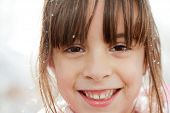 Close Up Of A Happy Little Girl With Snowflakes In Her Hair