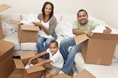 African American family, parents and son, unpacking boxes and moving into a new home, The adults are unpacking crockery and houseware.
