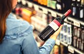 Woman Reading The Label Of Red Wine Bottle In Liquor Store Or Alcohol Section Of Supermarket. Shelf  poster