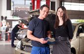 Portrait of a man mechanic with a woman customer going over the auto repair service report