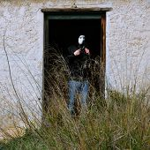 picture of pervert  - Man with white mask by broken door of abandoned house and overgrown plants - JPG