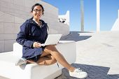 Portrait Of Carefree Young Student Using Laptop In Modern Campus. Asian Businesswoman Wearing Glasse poster