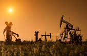 Silhouette of oil pump with sunset