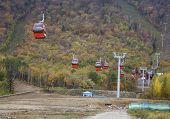 red overhead cable car over mountains in autumn