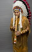 stock photo of musical instruments  - Portrait of a native american playing at a flute in a studio - JPG